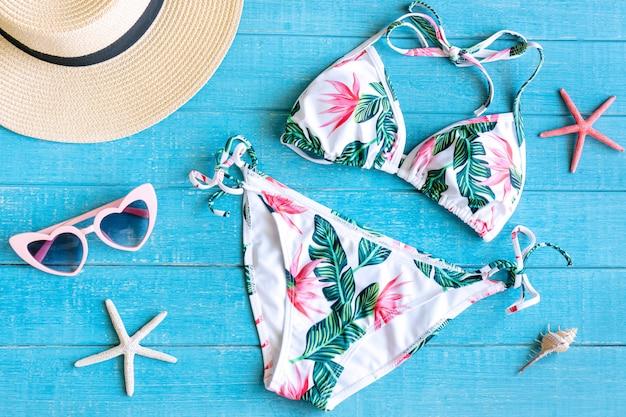 Płaskie ukształtowanie letnich przedmiotów z kolorowe bikini, okulary przeciwsłoneczne, słomkowy kapelusz i koral na niebieskim drewnianym stole, widok z góry. koncepcja lato