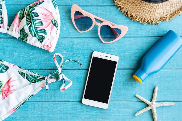 Płaskie ukształtowanie letnich przedmiotów z kolorowym bikini, smartfonem, okularami przeciwsłonecznymi, kapeluszem plażowym, kremem do opalania i smartfonem