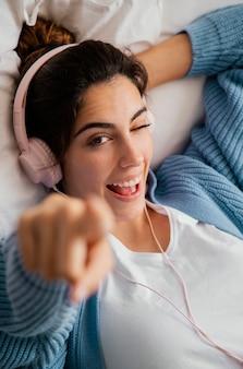 Płaskie ukształtowanie młodej kobiety, słuchanie muzyki na słuchawkach i wskazując