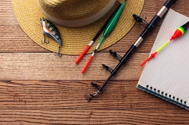 Płaskie ukształtowanie niezbędnych akcesoriów wędkarskich z czapką i przynętą