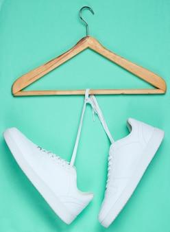 Płaskie ukształtowanie nowoczesnych białych trampek buty z wieszakiem na pastelowym tle.