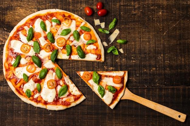 Płaskie ukształtowanie pizzy na drewnianym stole