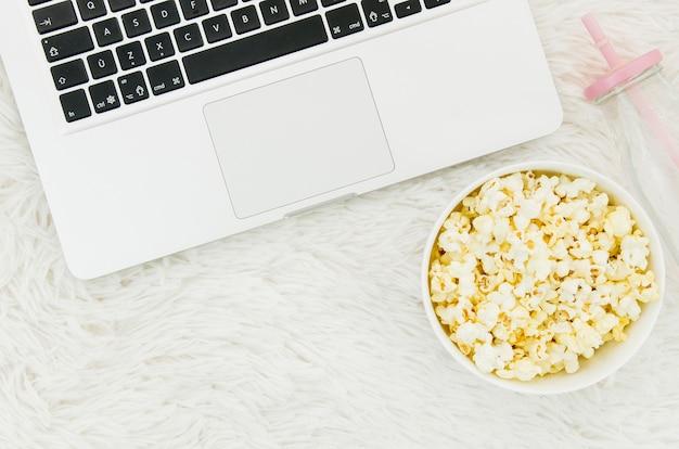 Płaskie ukształtowanie popcornu i laptopa do koncepcji kina