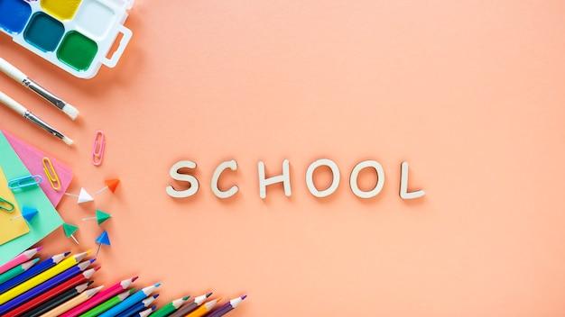Płaskie ukształtowanie przyborów szkolnych na kolor tła. powrót do koncepcji szkoły.