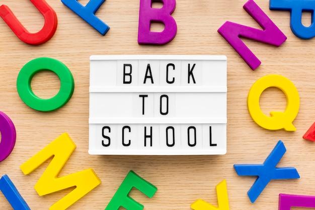 Płaskie ukształtowanie przyborów szkolnych z lekkim pudełkiem i literami