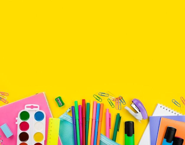 Płaskie ukształtowanie przyborów szkolnych z ołówkami i akwarelą