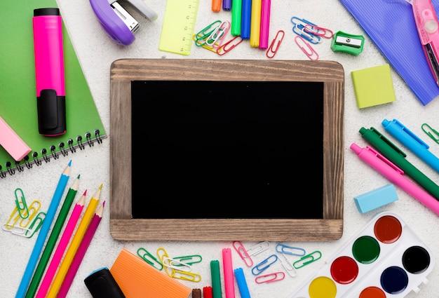 Płaskie ukształtowanie przyborów szkolnych z ołówkami i tablicą