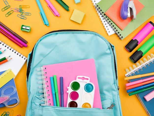 Płaskie ukształtowanie przyborów szkolnych z plecakiem i kolorowymi ołówkami