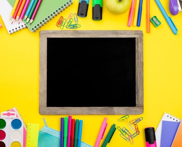 Płaskie ukształtowanie przyborów szkolnych z tablicą i jabłkiem