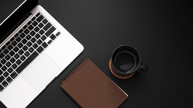 Płaskie ukształtowanie pulpitu z laptopem i filiżanką kawy