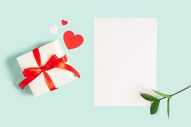 Płaskie ukształtowanie pustego papieru listowego z prezentem valentine