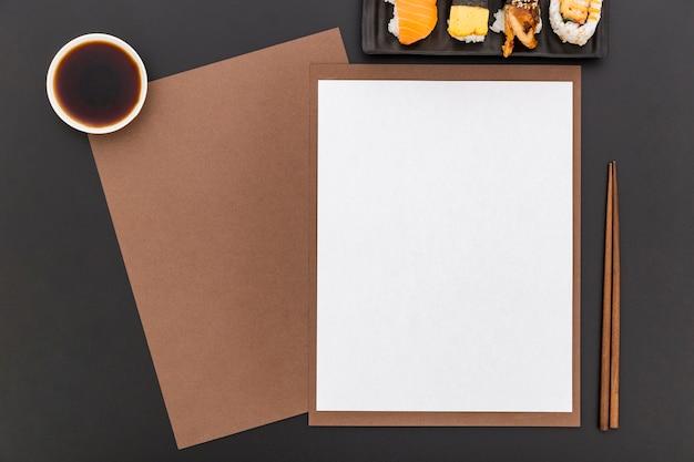 Płaskie ukształtowanie pustego papieru menu z sushi i sosem sojowym