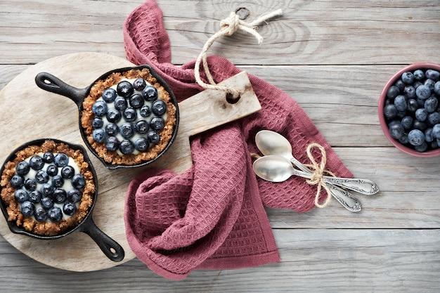 Płaskie ukształtowanie pysznych tartalek z jagodami z waniliowym kremem