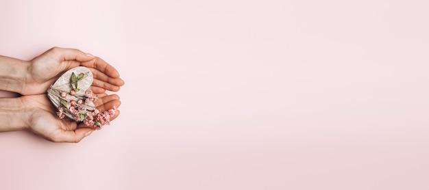Płaskie ukształtowanie rąk kobiety trzymając drewniane serce na tle delikatny kolor.