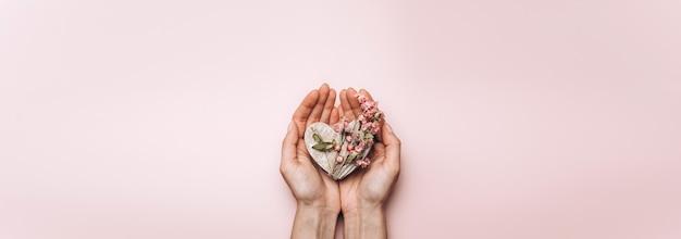 Płaskie ukształtowanie rąk kobiety trzymającej drewniane serce na ścianie w delikatnym kolorze.