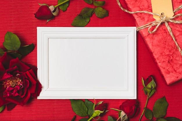 Płaskie ukształtowanie ramy z różami i prezentem