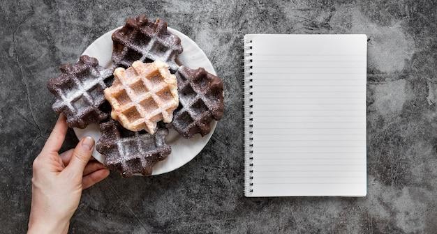 Płaskie ukształtowanie ręki trzymającej talerz gofrów i notebooka