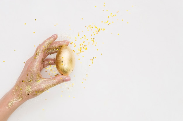 Płaskie ukształtowanie ręki trzymającej złote jajko wielkanocne z brokatem i miejsce