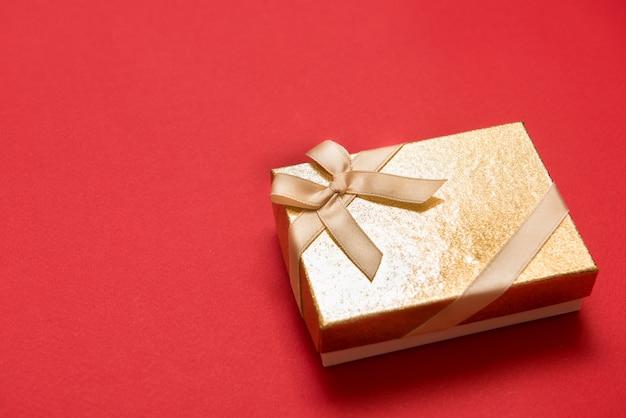 Płaskie ukształtowanie romantyczny prezent ozdobiony wstążką na czerwonym tle