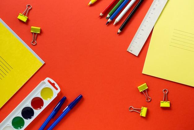 Płaskie ukształtowanie różnych przyborów szkolnych na czerwonym tle. miejsce na tekst