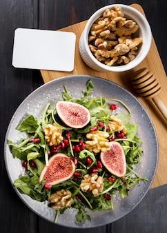 Płaskie ukształtowanie sałatki figowej jesienią na talerzu z orzechami włoskimi
