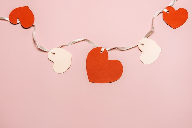 Płaskie ukształtowanie serc papieru na kolorowym tle. koncepcja miłości.