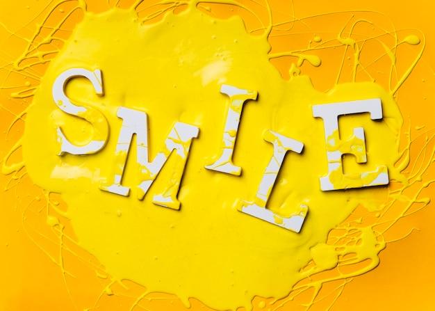 Płaskie ukształtowanie słowa uśmiech z farbą