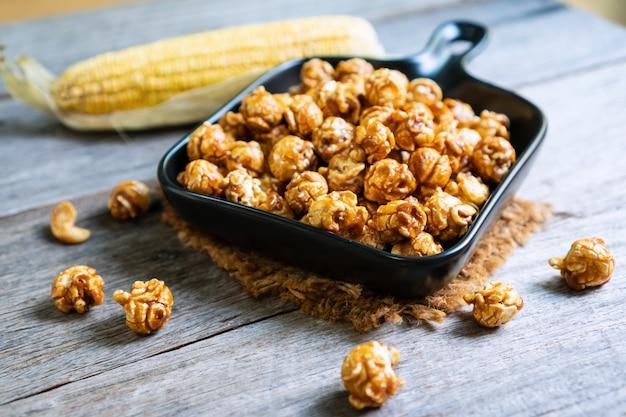 Płaskie ukształtowanie smacznego popcornu karmelowego w czarnym talerzu ceramicznym patelni i kukurydzy na drewnianym stole, z bliska.