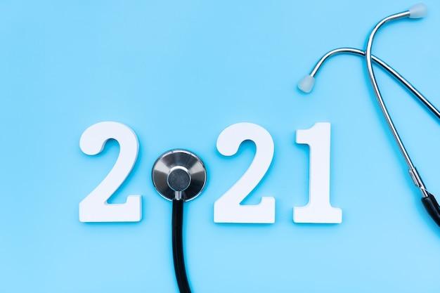 Płaskie ukształtowanie szczęśliwego nowego roku 2021. numer 2021 ze stetoskopem na niebieskiej ścianie. zdrowie medyczne i nowa koncepcja normalnego stylu życia. skopiuj miejsce, widok z góry