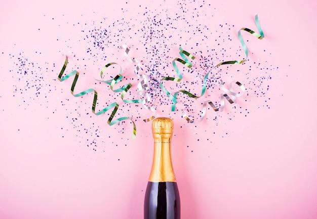 Płaskie ukształtowanie uroczystości. butelka szampana z kolorowymi serpentynami na różowo