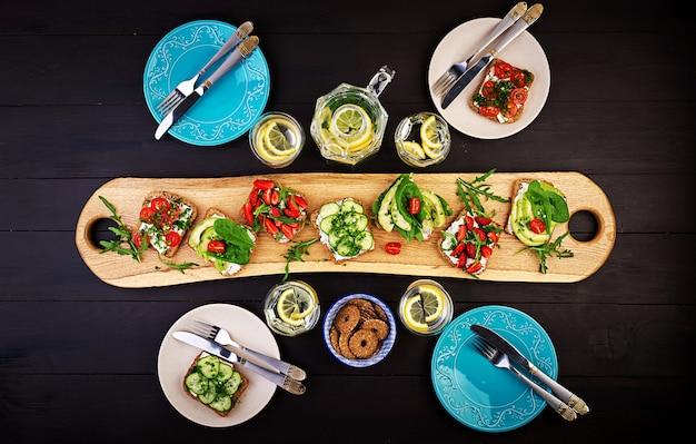 Płaskie ukształtowanie zdrowego wegetariańskiego stołu. kanapki z pomidorem, ogórkiem, awokado, truskawką, ziołami i oliwkami, przekąski. czyste jedzenie, wegańskie jedzenie