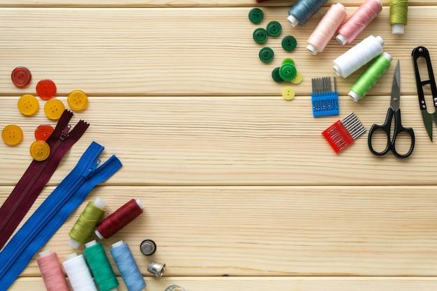 Płaskie ułożenie akcesoriów dla krawca. zestaw do szycia na podłoże drewniane.
