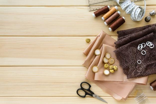 Płaskie Ułożenie Akcesoriów Do Szycia. Tkanina, Nici I Narzędzia Krawieckie Na Drewnie Premium Zdjęcia