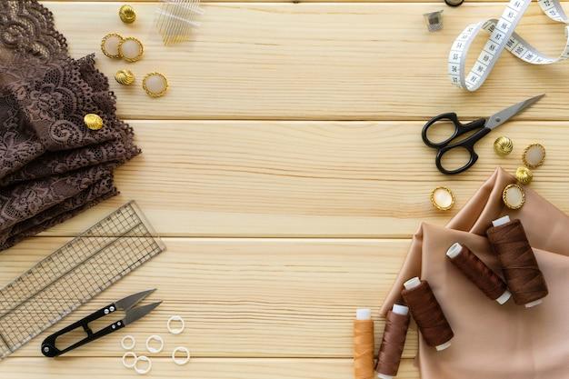 Płaskie ułożenie akcesoriów do szycia. tkaniny, nici i narzędzia krawieckie na podłoże drewniane, miejsca na tekst.