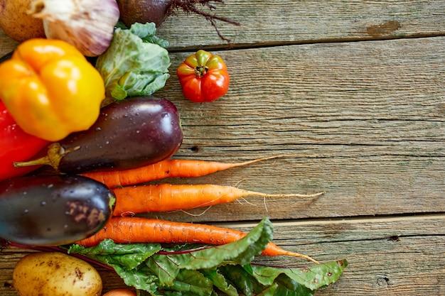 Płaskie ułożenie asortymentu świeżych warzyw, bio zdrowej, ekologicznej żywności na drewniane tła, styl rynku wiejskiego, produkty ogrodowe, dieta wegetariańska, czyste jedzenie.