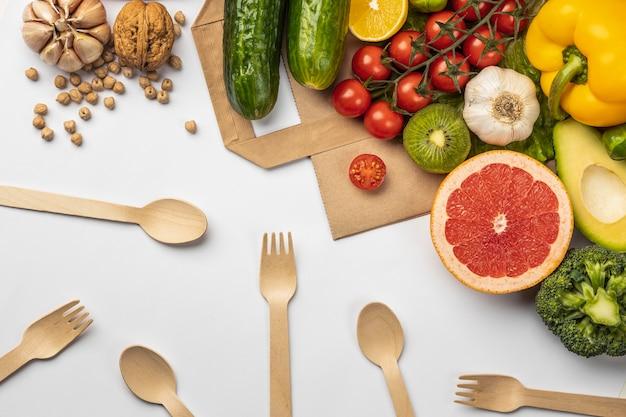 Płaskie ułożenie asortymentu warzyw z papierową torbą i drewnianymi sztućcami