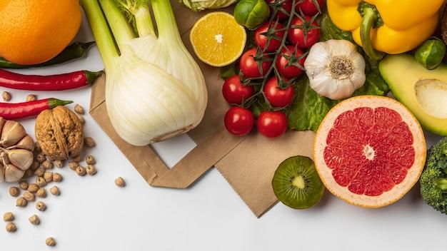 Płaskie ułożenie asortymentu warzyw z papierową torbą i miejscem na kopię