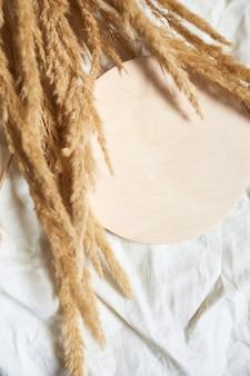 Płaskie ułożenie beżowej trzciny trawa pampasowa na tle białego obrusu tekstylnego, piękny wzór w neutralnych kolorach, minimalistyczna, stylowa, koncepcja trendu, widok z góry
