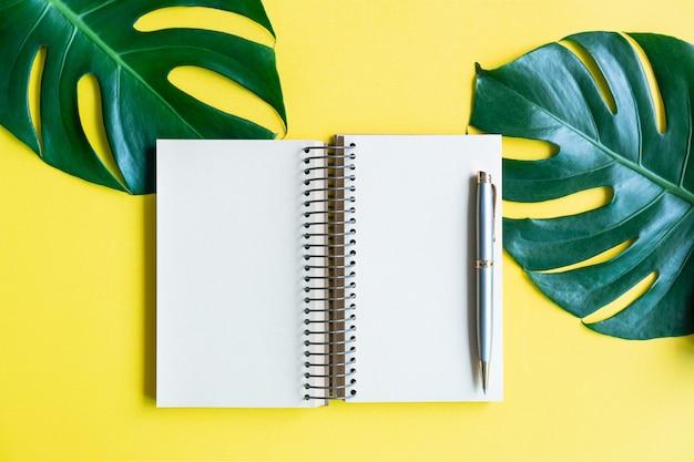 Płaskie ułożenie botebook i zielonych liści na żółtym tle koloru. widok z góry i kopiowanie miejsca na tekst.