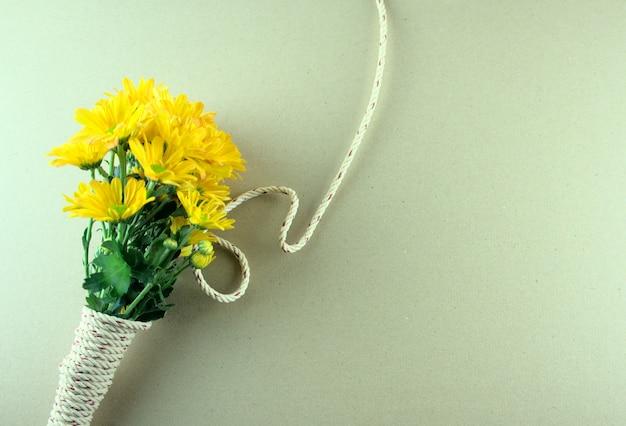 Płaskie ułożenie bukietu żółtych mam lub kwiatów chryzantemy wiążących liną na szarym tle
