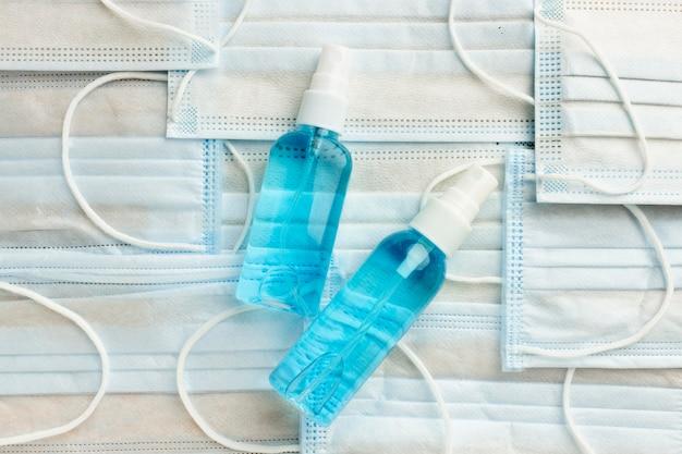 Płaskie ułożenie butelek ze środkiem dezynfekującym do rąk na maskach medycznych