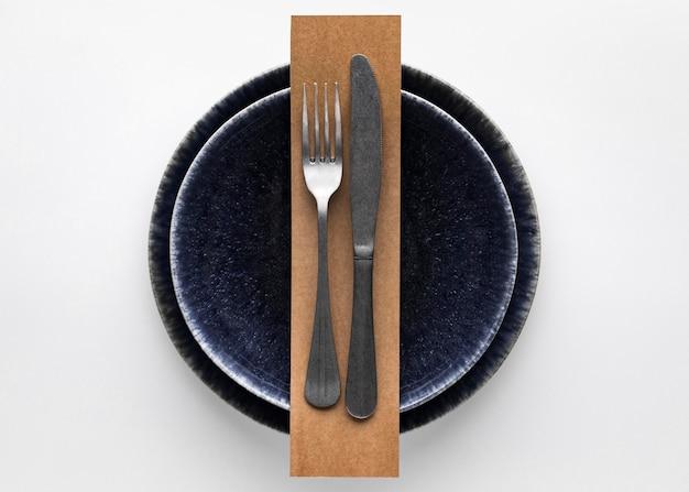 Płaskie ułożenie ciemnej zastawy stołowej z widelcem i nożem