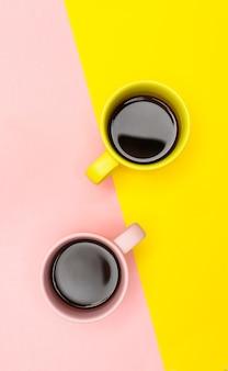 Płaskie ułożenie dwóch filiżanek kawy w kolorze różowym i żółtym