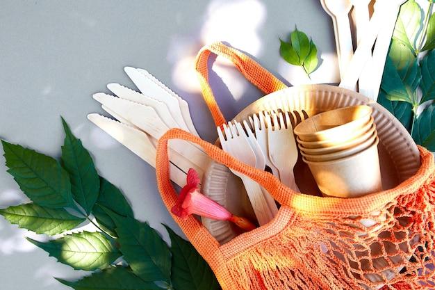 Płaskie ułożenie ekologicznego papieru rzemieślniczego i drewnianej zastawy stołowej, letnie światło słoneczne, zero odpadów, wolne od plastiku i ekologiczne życie, papierowe kubki, naczynia, torba