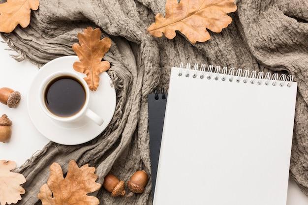 Płaskie ułożenie filiżanki kawy z tekstylnymi i jesiennymi liśćmi