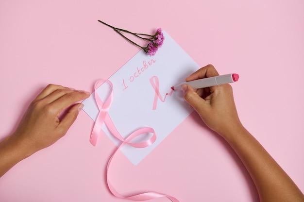 Płaskie ułożenie kobiecej dłoni trzymającej pisak pisze 1 października i rysuje na papierze różowy symbol miesiąca świadomości raka piersi, różową wstążkę z niekończącym się końcem leżącą na różowym tle