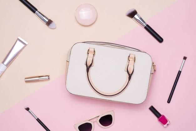 Płaskie ułożenie kobiecych akcesoriów modowych i białej torebki na pastelowym tle z copyspace