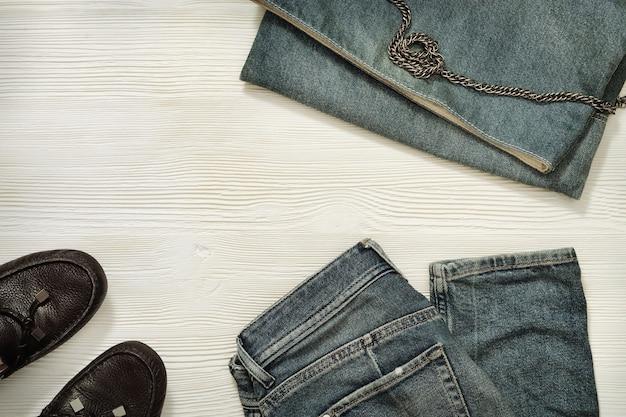 Płaskie ułożenie kobiet casualowych strojów na białym drewnianym tle niebieskie dżinsy i dżinsowa mała torba