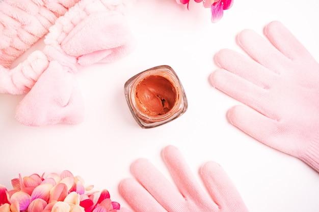 Płaskie ułożenie kosmetyków pielęgnacyjnych, kremu do twarzy i ciała w kolorze koralowym lub różowym w otoczeniu akcesoriów pielęgnacyjnych. rękawiczki, opaska i pąki z różowych kwiatów. układ na białym tle, zabiegi kosmetyczne w domu