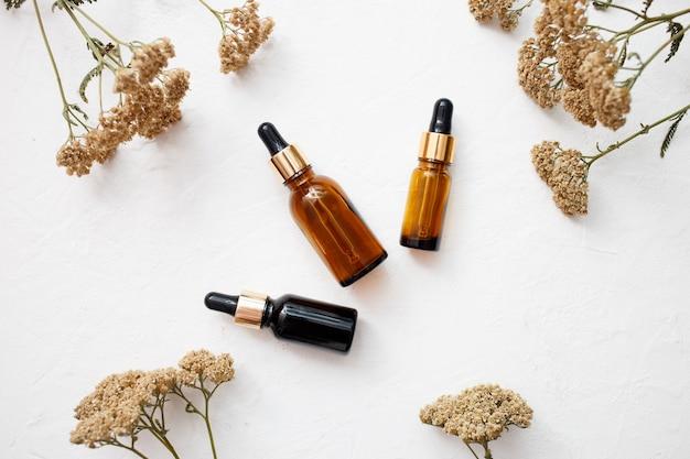 Płaskie ułożenie kroplomierzy szklanych butelek produktów do pielęgnacji skóry olejków eterycznych do makiety w minimalistycznym stylu na białym tle.